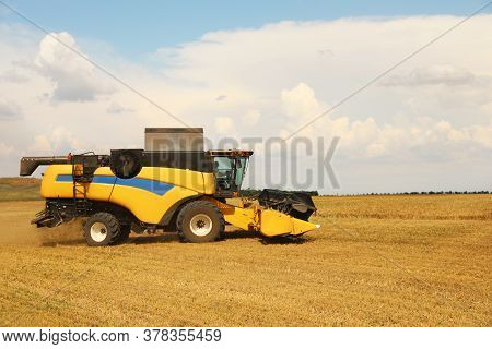Modern Combine Harvester In Field On Sunny Day. Agricultural Machinery