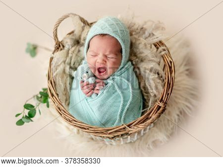 Adorable newborn yawning while rest in basket