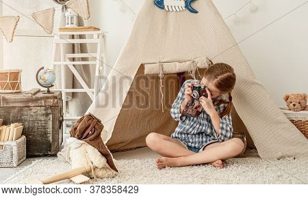 Nice little girl photographing plush teddy on wigwam installed in playroom background