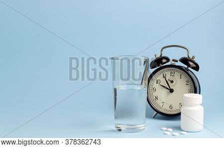 Jar Of Pills, Water And A Clock On A Blue Background. Time To Take Pills. Insomnia.