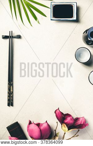 Asian food background - sake and chopsticks on a slate board over grey concrete background. Top view, flat lay