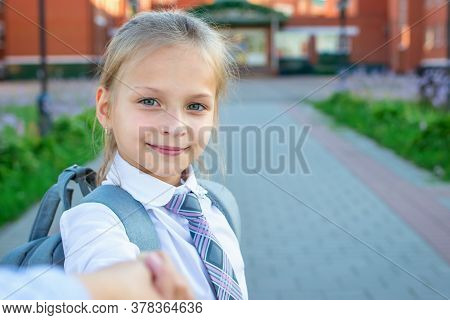 Close Up Of A Happy Smiling Girl That Goes To The Elementary School. Child In White Blouse Is Holdin