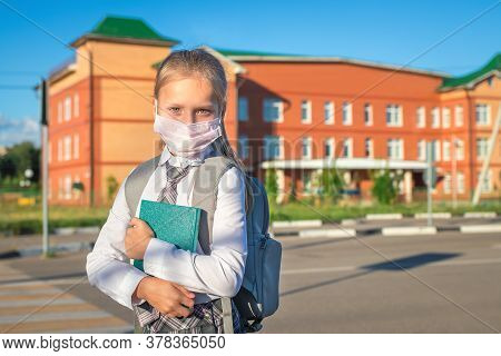 Little Girl In Medical Face Mask Goes To The Elementary School. Child With A Grey Backpack, Green Bo