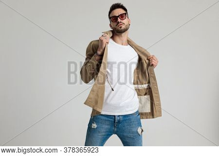 cool unshaved young guy wearing sunglasses, holding and adjusting jacket, standing in a fashion pose on grey background