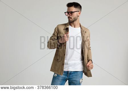 attractive young casual man in jacket wearing sunglasses, looking to side, holding and arranging jacket, standing and posing on grey background