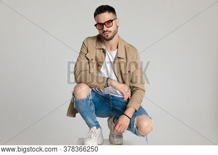 young casual fashion model in jacket wearing sunglasses, holding elbow on knee in a fashion pose, bending knee and crouching on grey background
