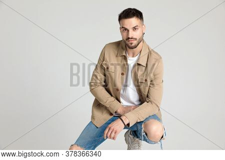 attractive young casual man in jacket holding elbow on knee in a fashion pose, smiling and crouching on grey background