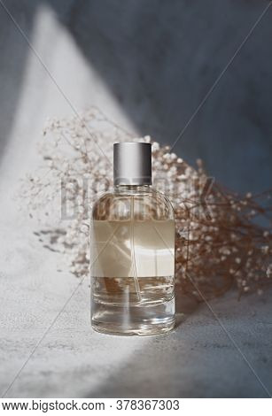 Beautiful Transparent Fragrance Bottle From Glass In Contrast Light. Vertical Shot With Tiny Flowers