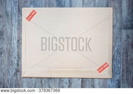 Old And Dirty Brown Paper Big Size Envelope On Wooden Background Marked Red Do Not Bend, Mail Postag