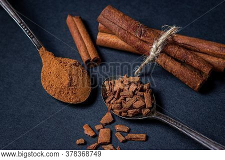 Cinnamon On A Black Background. A Spoonful Of Young Cinnamon Lies Next To A Spoonful Of Crushed Cinn