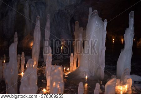 Stalagmites From Ice Illuminated By Candles