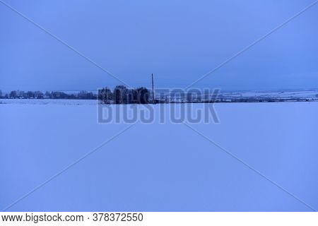 Snow-covered Expanse Of Field With Trees On The Horizon