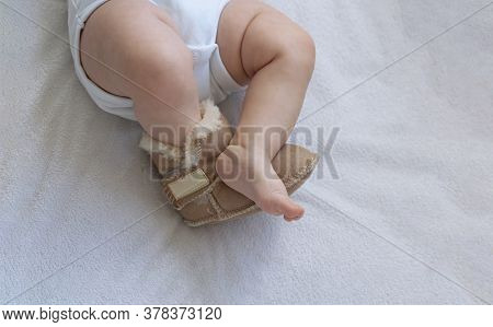 Feet Of A Newborn Toddler Close-up On The Bed. On One Foot Boots Made Of Leather And Fur. The Second