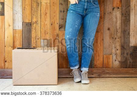 Cardboard Moving Boxes In Empty Room With Wooden Wall Background And Copy Space, Moving In New Flat