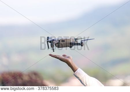 The Drone And Photographer Human Hand. Drone Copter Flying With Digital Camera Near Hand.