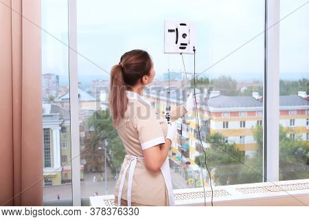 A Uniformed Maid Turns On A Window Cleaner Robot. . Photos In The Interior. The Concept Of Cleaning