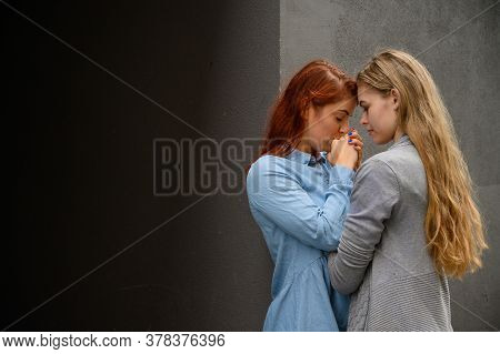 Passionate Loving Lesbian Couple. Two Beautiful Young Women Hugging Tenderly Outdoors Against A Gray