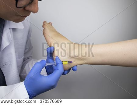 An Orthopedic Surgeon Injects Medicine Into The Achilles Tendon To Relieve Pain. Help Treat Sprains,