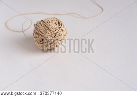 A Ball Of Thin Beige Rope (thick Thread) On A Light Gray Background