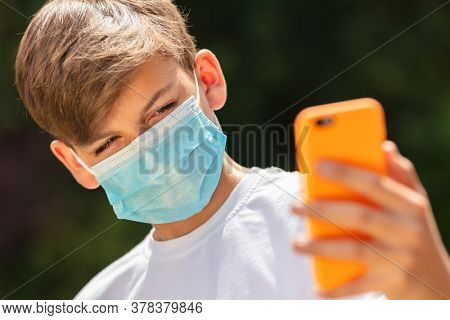Boy teenager teen male child wearing a face mask outside during the Coronavirus COVID-19 virus pandemic while using his mobile cell phone for a selfie for social media