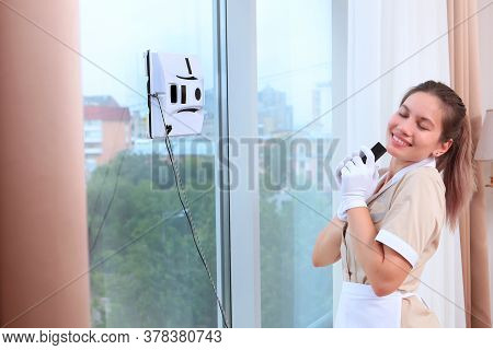 A Happy Young Maid In Uniform Controls A Robot Window Cleaner. Clear Window. Photos In The Interior.