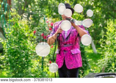 Close-up And Soft Focused Image Of A Soap Bubbles. Man Artist And Magician Shows A Performance With