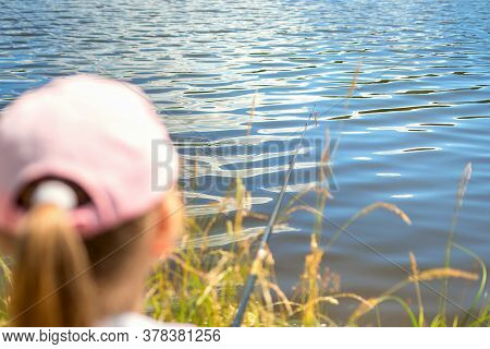 Close Up Of Fishing Rod And Red Float In The River. The Girl In The Cap Catches Fish And Looks At Th