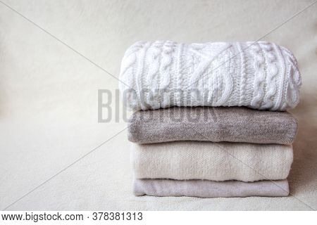 A Stack Of Beige And White Sweaters Lie On A Light Beige Fabric Background. Folded Soft Warm Clothes