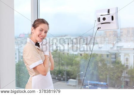 A Smiling Maid Remotely Controls A Robot Window Cleaner. Room Service. Cleaning In The Hotel Or In T