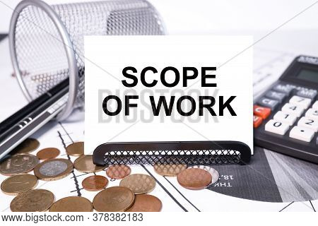 Scope Of Work. Inscription On A White Business Card Against The Background Of Financial Charts Of A