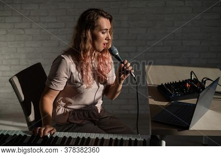 A Young European Woman Sings Into A Microphone And Accompanies On An Electronic Piano. The Girl Shoo