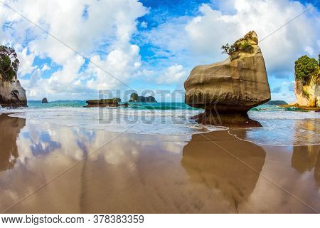 Coromandel Peninsula. Cathedral Cave on the North Island. Bizarre clouds and coastal cliffs reflected in the tidal waters of the Pacific Ocean. The concept of exotic, ecological and photo tourism