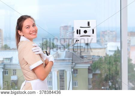 A Satisfied Maid Remotely Controls A Robot Window Cleaner. Room Service. Cleaning In The Hotel Or In