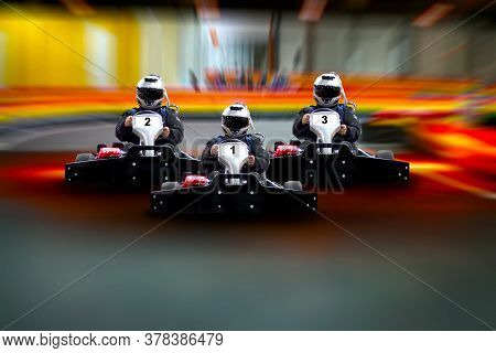 Three Riders Go Kart Speed Rive Indoor Race On The Background Of The Track. Go Kart Indoor, Cart Rac