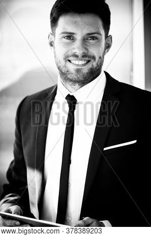 Business concept. Happy young businessman standing in office holding wireless touchpad tablet computer. Man in suit indoors using internet device on glass background. Black and white, monochrome.