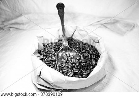 Paper Bag With Roasted Coffee Beans And A Very Old Antique Spoon With Patina