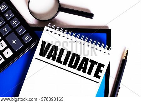 The Word Validate Is Written In A White Notebook On A White And Blue Background Next To A Calculator