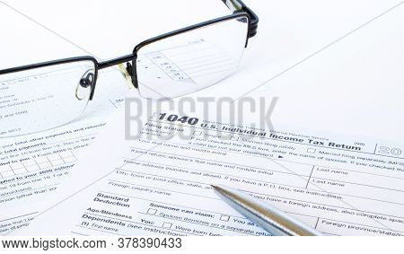 Us Tax Form 1040 With A Silver Pen And Glasses