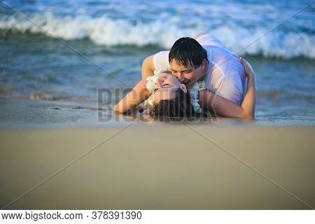 A Newlywed Couple In Wet Clothes Flirting, Hugging And Kissing While Lying On A Beach. Honeymoon In