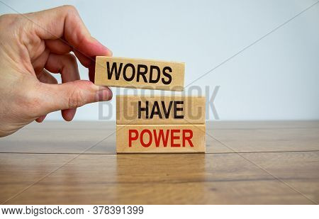 Male Hand Placing A Block With Word 'words' On Top Of A Blocks Tower With Words 'have Power'. Wooden