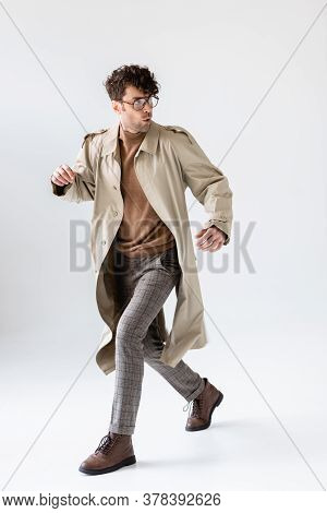 Trendy, Frightened Man Running And Looking Back Isolated On Grey
