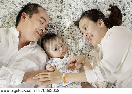 Asian Parents Playing With Baby Concept, Young Vietnamese Man And Woman Smiling And Interacting With