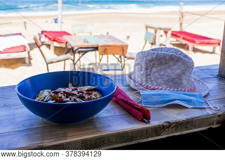 Protective Mask On The Table With Food. Open Restaurant Sea View. Healthy Fresh Nutrition. Summer Be