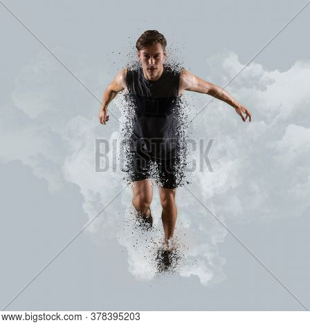 Sporty young man running on smoke background. Sports banner. Shatter effect