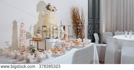 Candy Bar At The Banquet. Wedding Table With Sweets, Cake, Pastries, Muffins, Sugar Treats. Event In