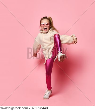 Blonde Hooligan Stomps Her Foot, Sways In A Pose, Is Indignant With Screams, On A Pink Studio Backgr