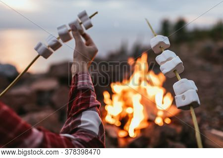 Cropped View Of Couple Holding Sticks With Puffy Marshmallows Near Bonfire