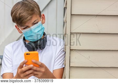 Boy teenager teen male child wearing a face mask outside during the Coronavirus COVID-19 virus pandemic while using his mobile cell phone and bluetooth wireless headphones