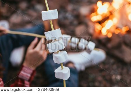 Selective Focus Of Puffy Marshmallows On Sticks Near Couple And Bonfire