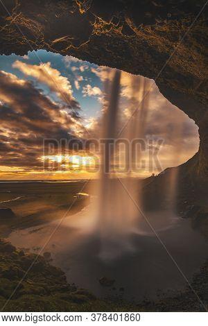 Summer Sunset Behind Seljalandsfoss Waterfall In Iceland